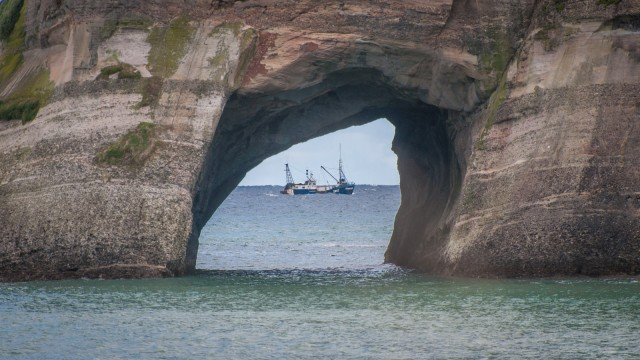 Perfect timing to catch the fishermen through the hole in the rock