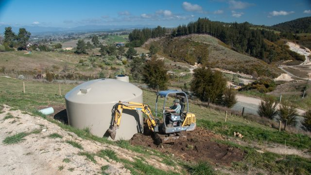 Finishing earth works around the extra water tank